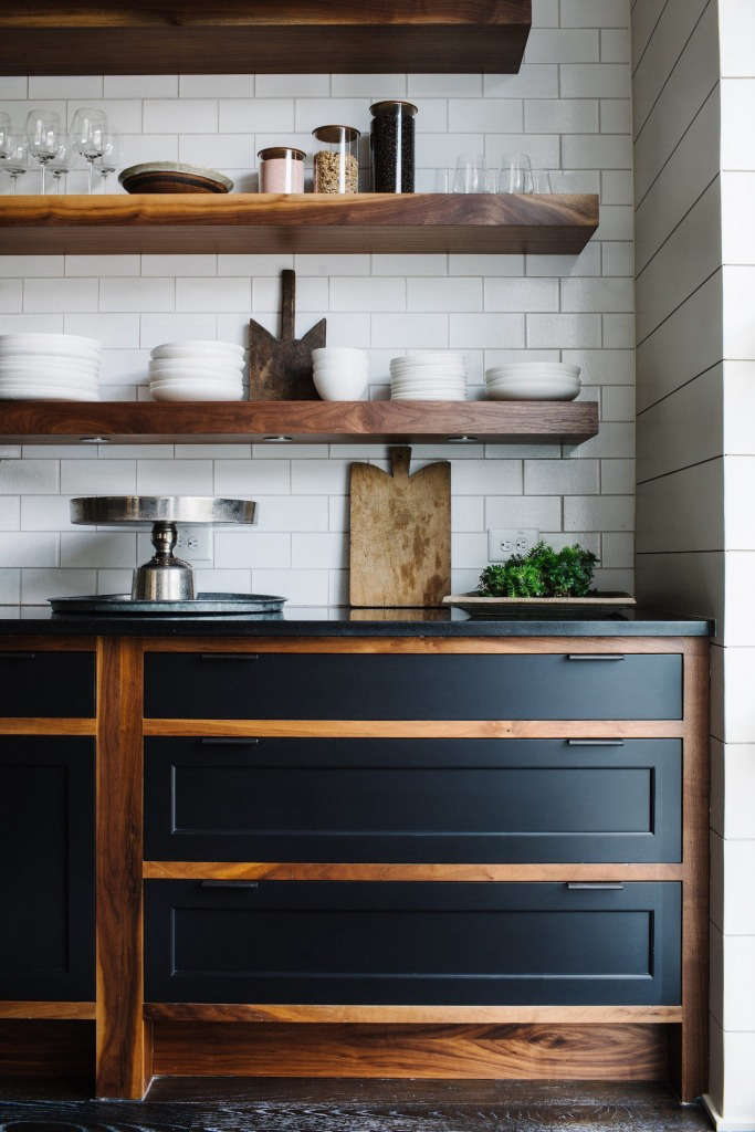 Floating shelves made of solid walnut hang over custom oiled walnut cabinets with painted maple fronts and steel handles.