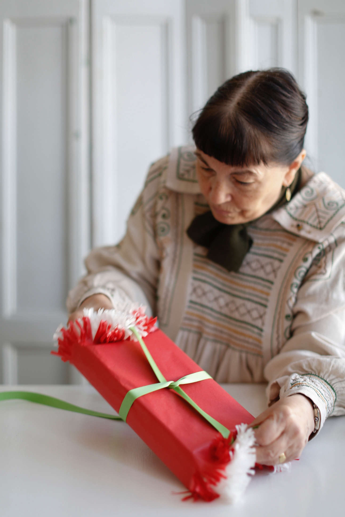 Step 3: Wrap a single, long piece of ribbon around the gift, starting with the closed edges and ending with the fringed sides. Wrap the ribbon right over the fringed ends, securing the open ends with the ribbon.