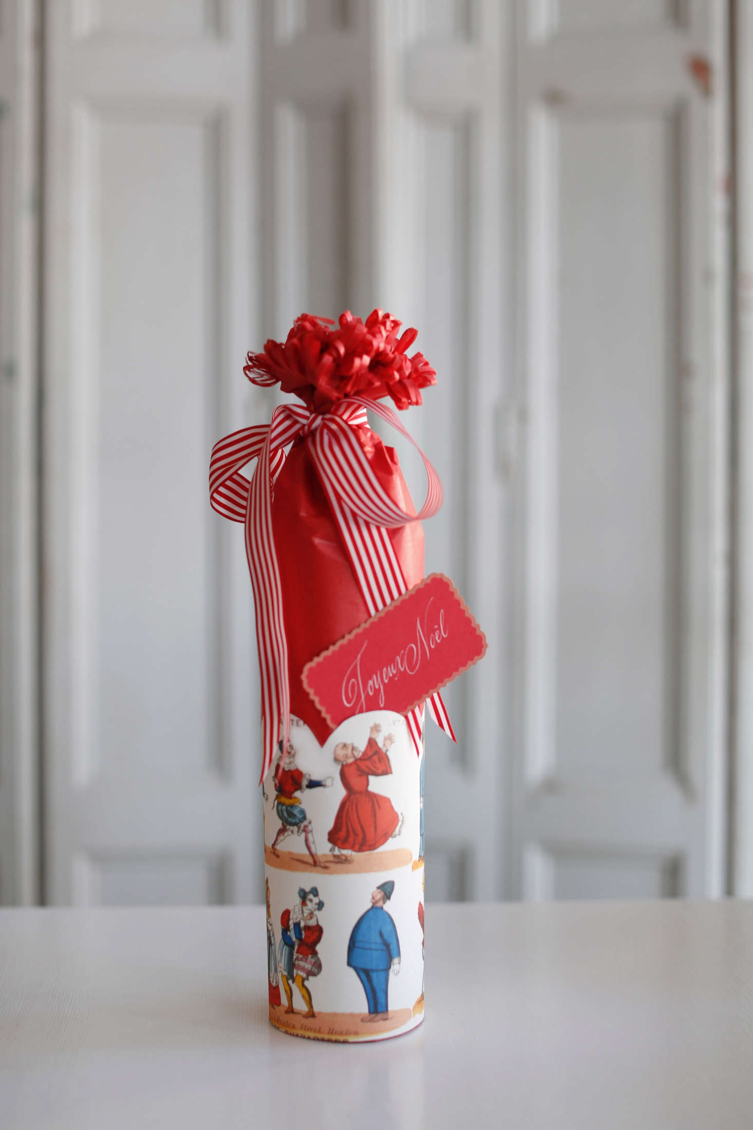A whimsical presentation for a wine bottle wrapped in tissue paper and topped with a French striped taffeta ribbon, English toy-print paper, and a hand-calligraphed Joyeux Noëlcard by the shop&#8
