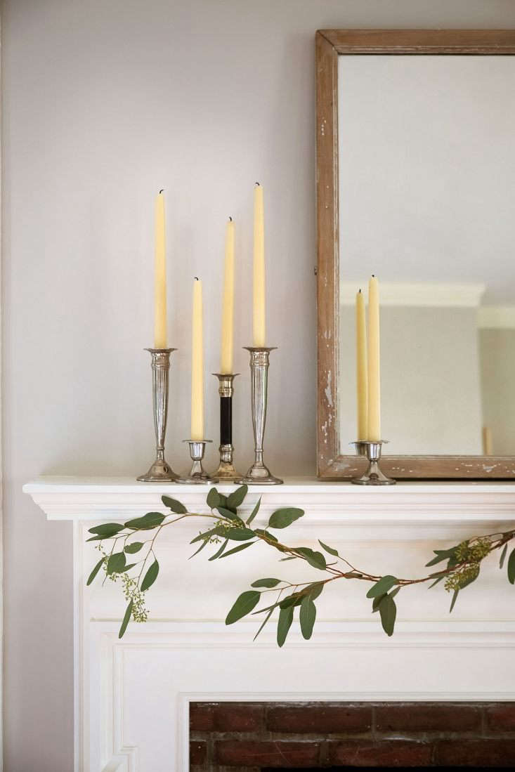 From there it was easy to style the rest of the mantel piece. The mirror, which weighs about 500 pounds and therefore never moves, maintained its position as the centerpiece. Complementing the silvery eucalyptus leaves, a grouping of sterling candlesticks with beeswax candles served as my requisite &#8