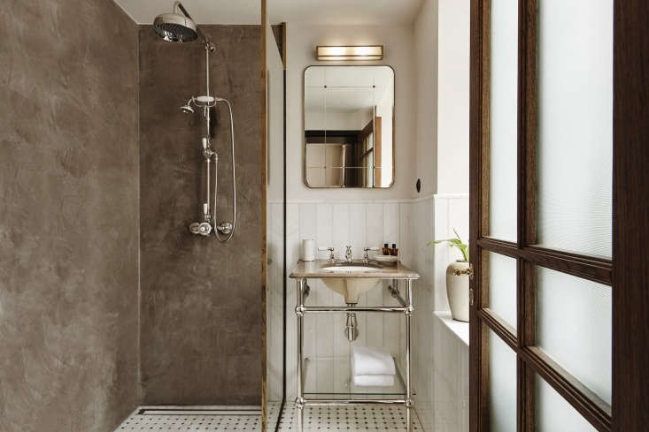 The shower walls are made of warm gray polished plaster and the tiles are all sourced from Greece; the vertically laid tiles are white Thassos marble. The pedestal sink is custom by Aquadomo in Denmark. Photograph courtesy of Lind & Almond.