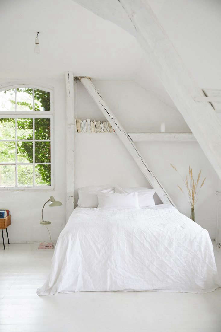 The all-white master bedroom is tucked under the rafters.