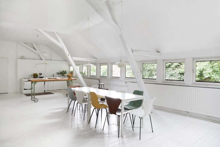 The extra-long table—two joined Ikea dining tables—is surrounded by Arne Jacobsen Series 7 and René Jean Caillett fiberglass chairs.