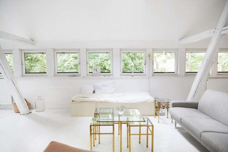 A homemade birch ply daybed and midcentury sofa anchor the living area. The brass-and-glass nesting tables have since been moved out—&#8