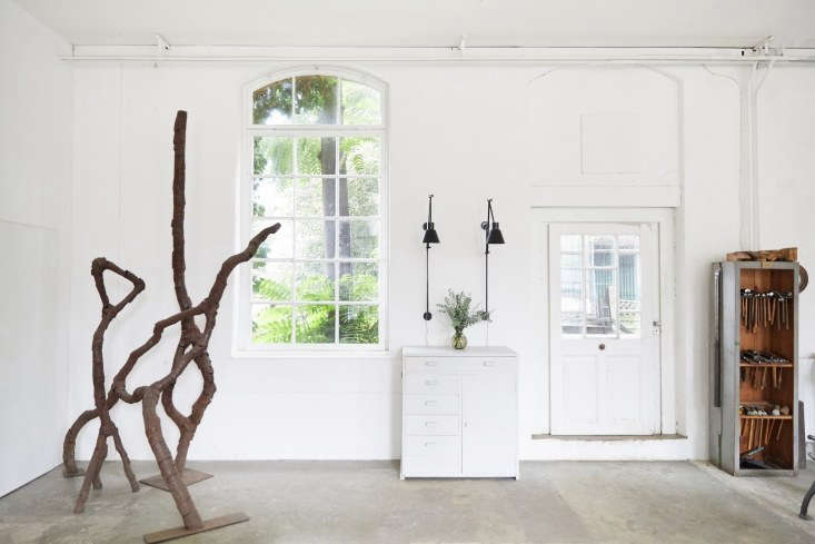 The 0-square-foot workshop is on the ground floor. When the couple took over the space, there was much to remove, including ivy-covered boards on all the giant windows and a stage.