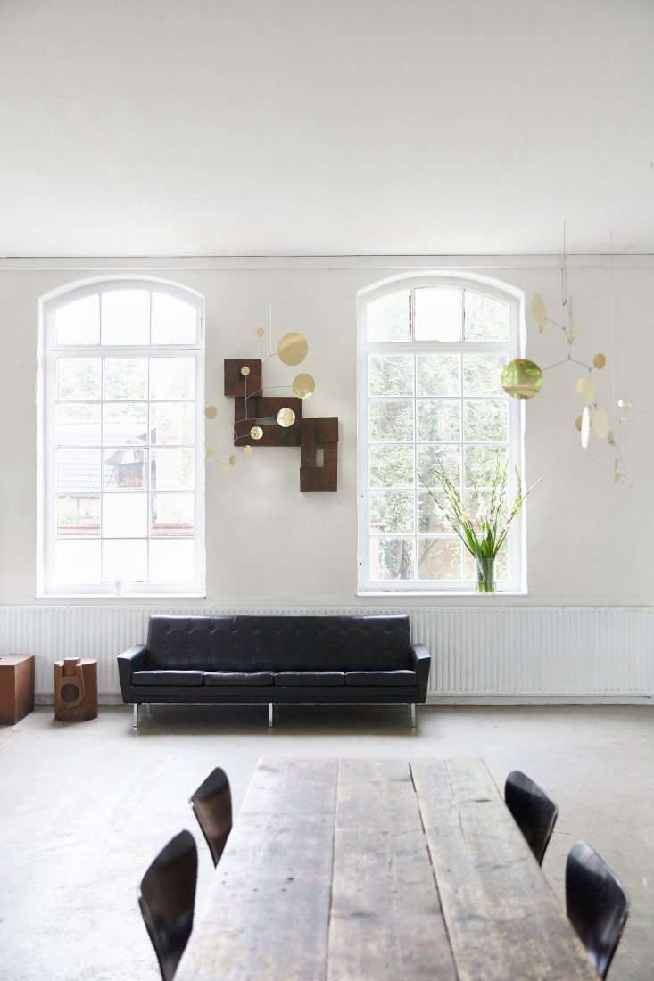 Above: A 60s black leather sofa, flat files, and Lappalainen Brass Mobiles.