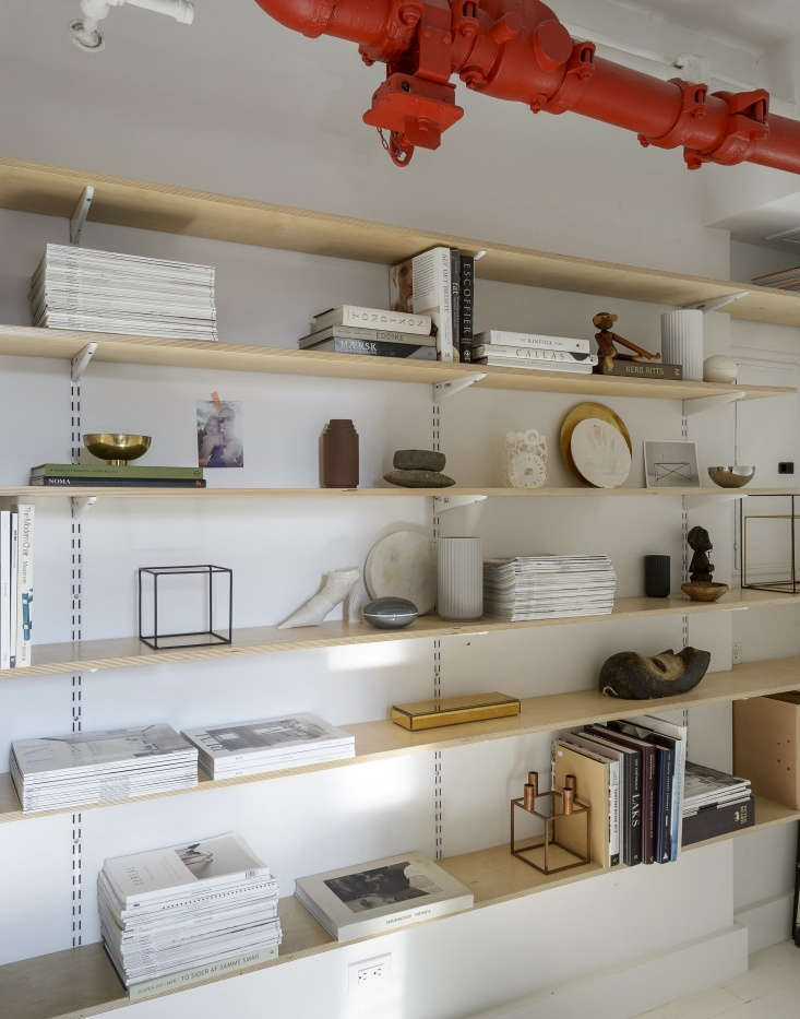 plywood shelves built from hardware store parts display not only books and maga 21