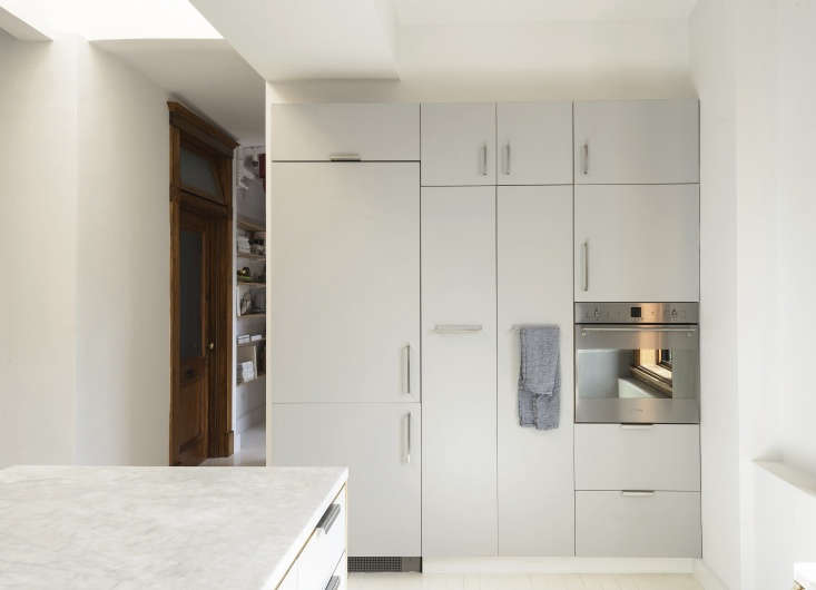 the fridge is concealed on the cabinet wall, which incorporates a smeg wall ove 11