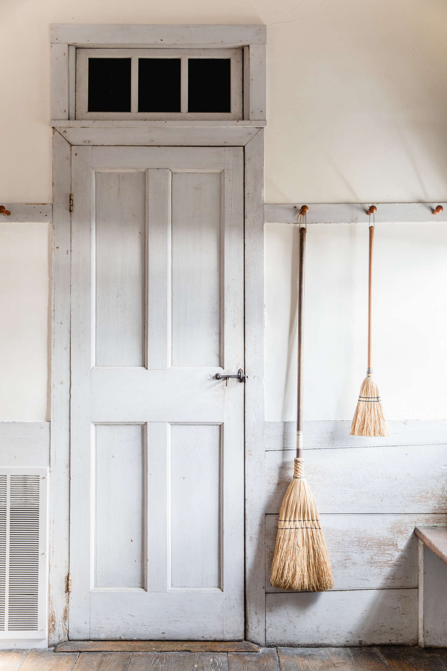 Peg rails keeps brooms at the ready in a Shaker schoolhouse. See In the Dwelling House:  Design Ideas to Steal from the Shakers.