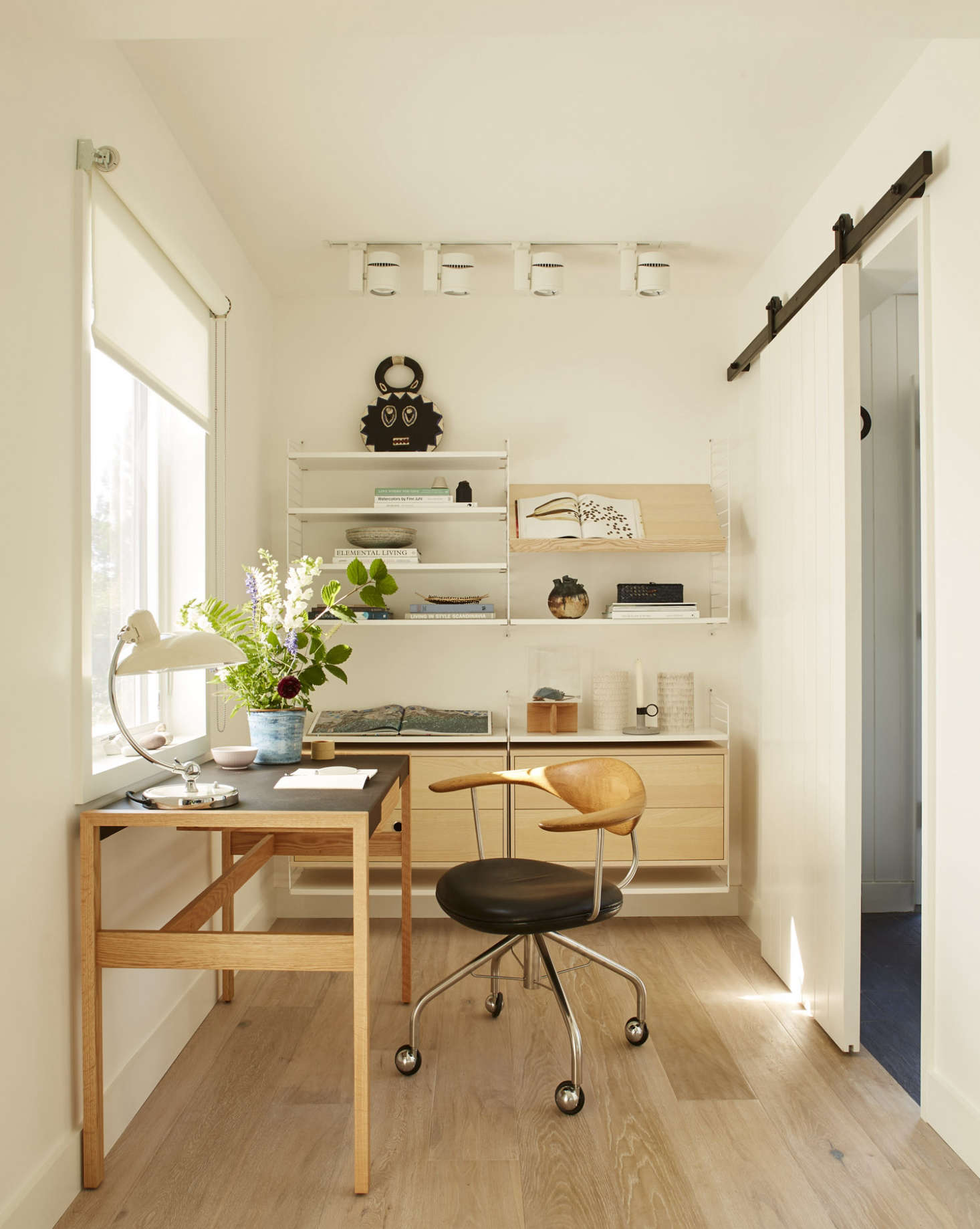 A small office accessible via sliding barn door off the entry hall sports a Risom Desk from DWR, shelving from Swedish company String, and a Kaiser Idell lamp from Fritz Hansen. The desk chair is a vintage Hans Wegner Swivel Chair. (&#8