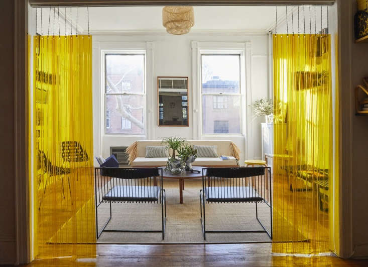 To divide the rooms, Valentin came up with an unconventional solution: yellow strip curtains, the kind typically used in industrial food storage facilities, suspended from a hospital drop chain sourced from a medical supply website. The black metal and leather chairs are Arnold Lounge Chairs from Valentin&#8