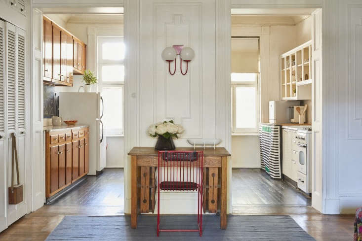 A Bogus Studio Arnold Chair in red is positioned in front of a Craftsman-style desk; the vintage double sconce is from a favorite resource of Valentin&#8