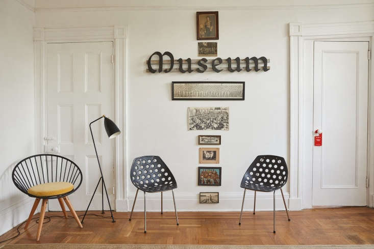 """Mounted on the wall is a museum sign Valentin got from a friend, conceptual artist Cyril Duval of Item Idem. The photos below are all group photos taken from the 30s to 60s collected, he says, """"from past lives in Paris, Tokyo, London, and Los Angeles."""" In front is theBogus Studio Circle Chair, aGreta GrossmanGrässhoppa Floor Lamp for Gubi, and two 60sCoquillage Chairs by Pierre Guariche for Meurop."""
