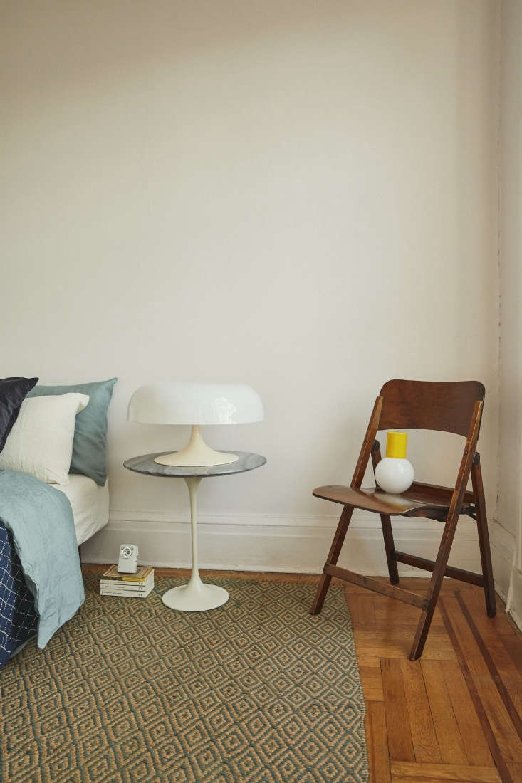 The pocket-sized bedroom has a rug sourced from Michele Varian in SoHo, a Saarinen replica table with a blue marble top, a vintage lamp in the style of Werner Panton, and bedding from Blue Blue Japan. The emergency flashlight is from the Tokyo Muji store and the yellowBedside Carafe is by Anna Karlin.