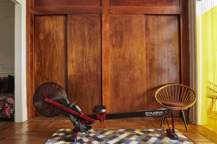 The home gym, opposite the desk, has a color-coordinatedStamina X Air Rower and Yngve Ekström Teak Chair. For the yoga mat, Valentin took an image of the Oaxacan rug under the desk and had a yoga mat printed with the same design.