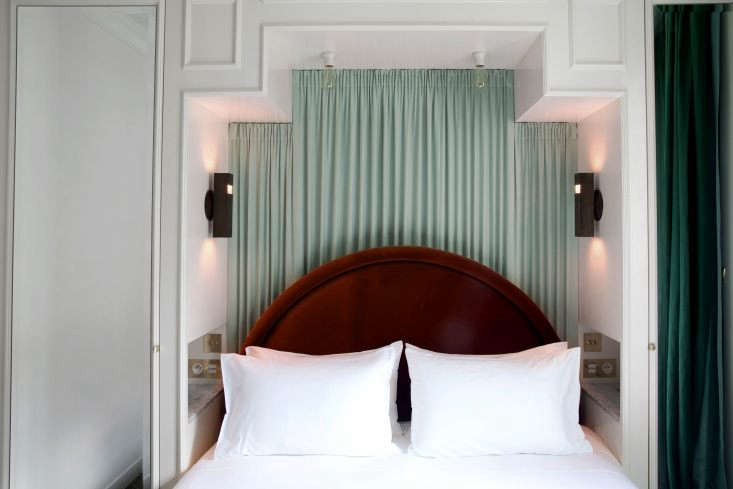 a compact room is fitted with a curtained backdrop. to make the tight space wor 17