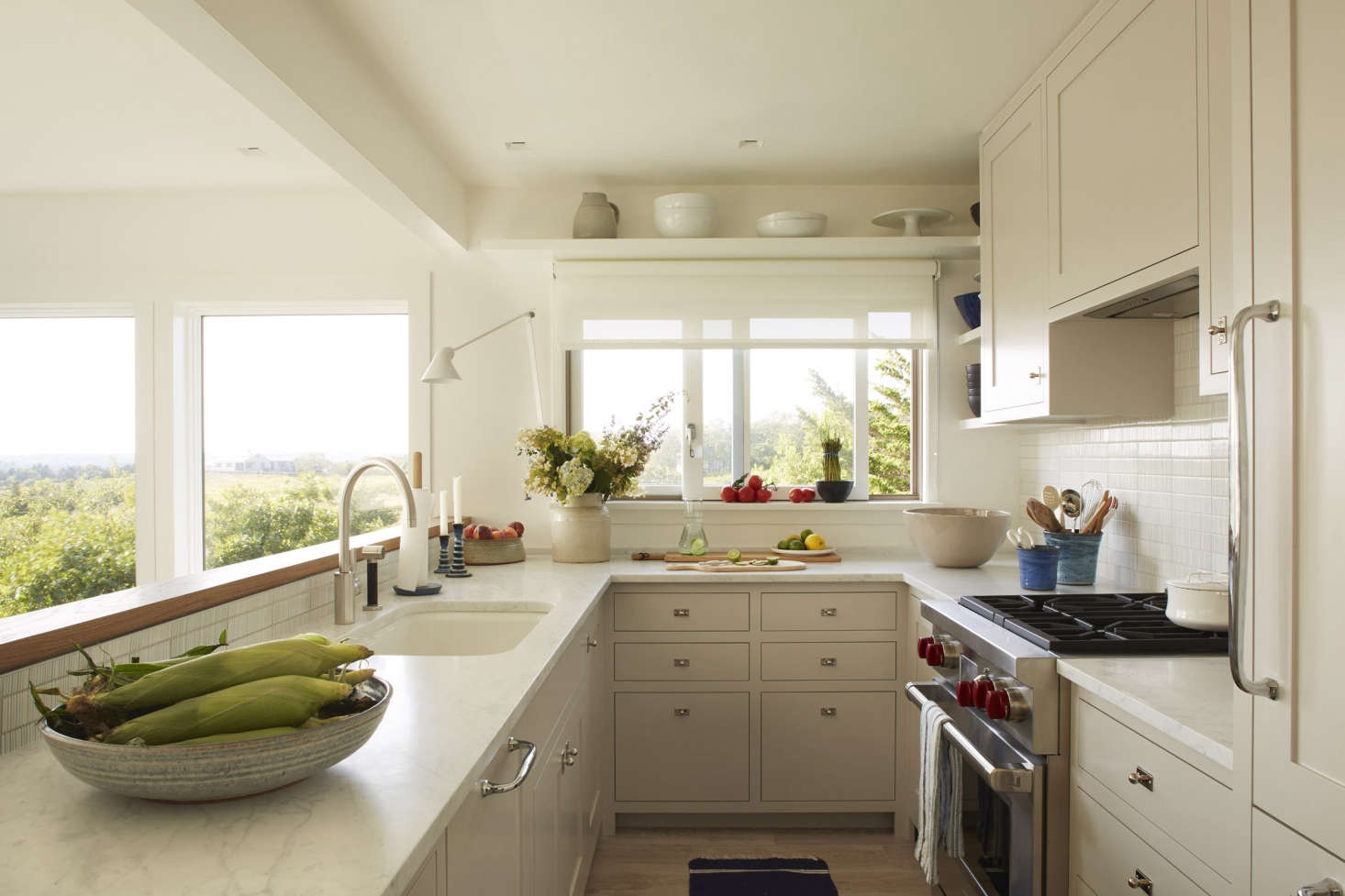 The kitchen, which overlooks the living room, kept its previous footprint but otherwise received a complete overhaul with Carrara marble countertops, a backsplash of textured white tile from Ann Sacks, and locally made Shaker-style cabinetry with Swedish hardware.