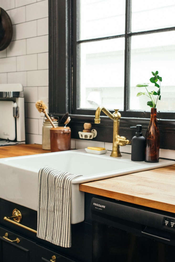 """The dark base cabinets are custom, fitted with cabinet pulls from Van Dyke's Restorers that Rosa stripped with a homemade concoction of salt, vinegar, and some time in the oven to dull the shiny brass finish. """"Our nanny at the time thought I was crazy!"""" she says.The apron-front kitchen sink is a now discontinued model fromIkea. The faucet is from Newport Brass."""
