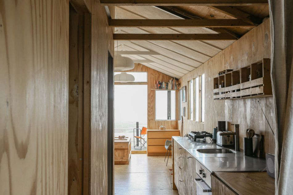 The view from the back of the house, through the kitchen, and onto the deck.Photograph byMarcia MihotichfromTwo London Creatives Shore Up a Tiny Beach House, Ikea Hack Kitchen Included.