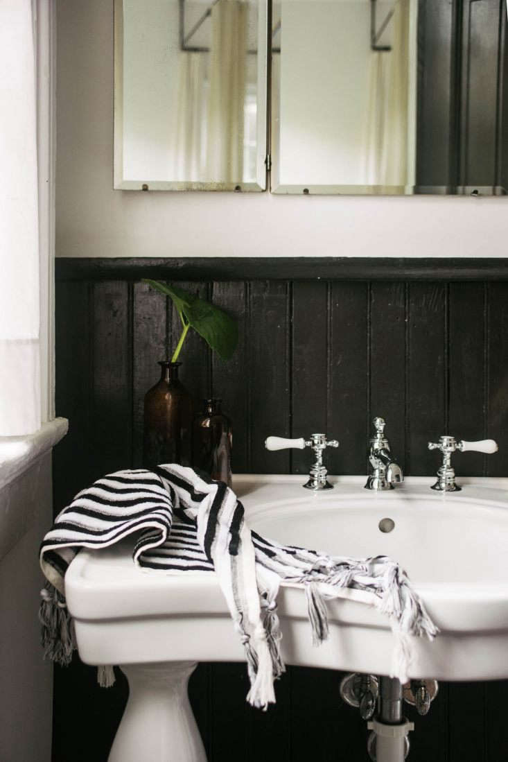 In the master bathroom: black-painted wood cladding, a triptych mirror, and afaucet from Waterworks'sJulia line.The sink is by Barclays.