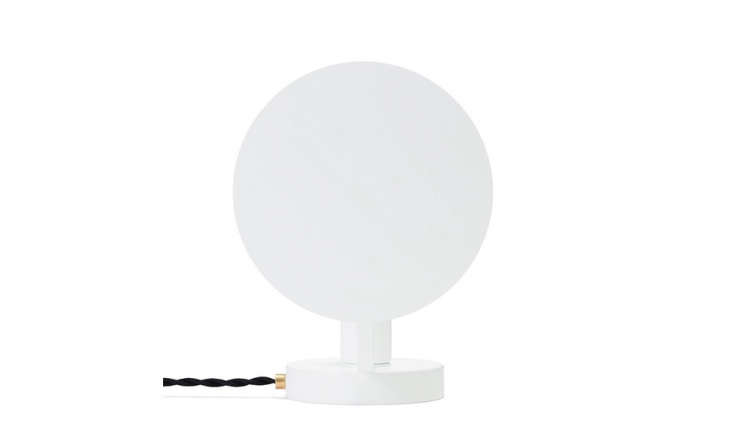 The OFS. Moon Lamp has a flat reflector disk atop the flush-mount body; it can be positioned in front of or behind the bulb, depending on whether you need direct light or a diffuse glow. It has a black braided cord and an on/off switch; $9.95.