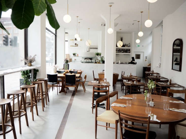 The restaurant, a gut remodel, is built out with stone floors and bright white walls to counteract the gloom of London weather. The globe lights are brass IC Lights by Michael Anastassiades for Flos.