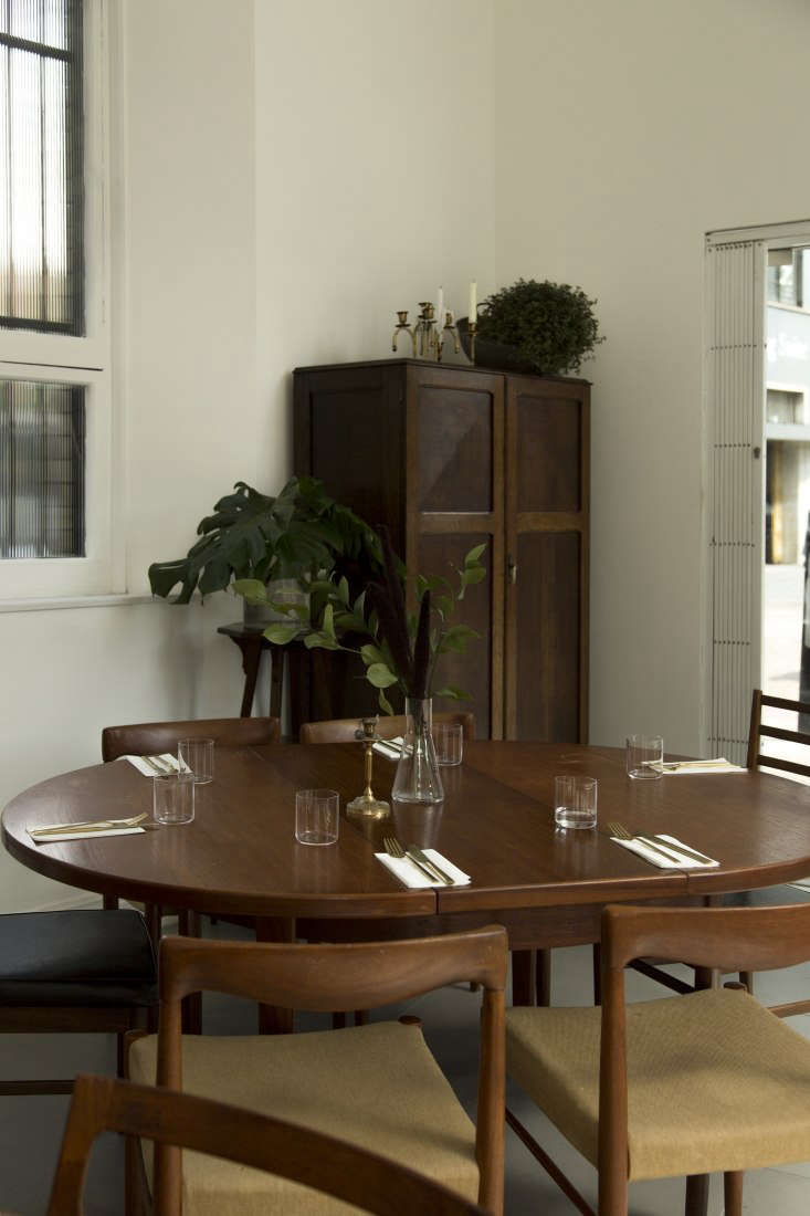 an antique walnut wardrobe acts as a service station storing flatware, linens,  15