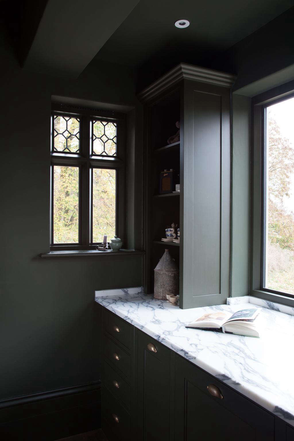 A stretch of countertop to the left of the sink is serene, thanks to a few tricks at work: Beneath the counter is (from left) a set of drawers, a cupboard for the trash bin, and the hidden dishwasher; the open shelving above is fitted with outlets for plugging in lighting and the owner&#8