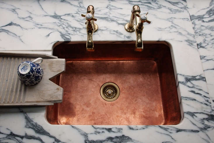 The undermount copper sink by Plain English is fitted with vintage brass taps sourced on eBay. An antiqueclothes washboard, now repurposed for dishes, sits alongside.