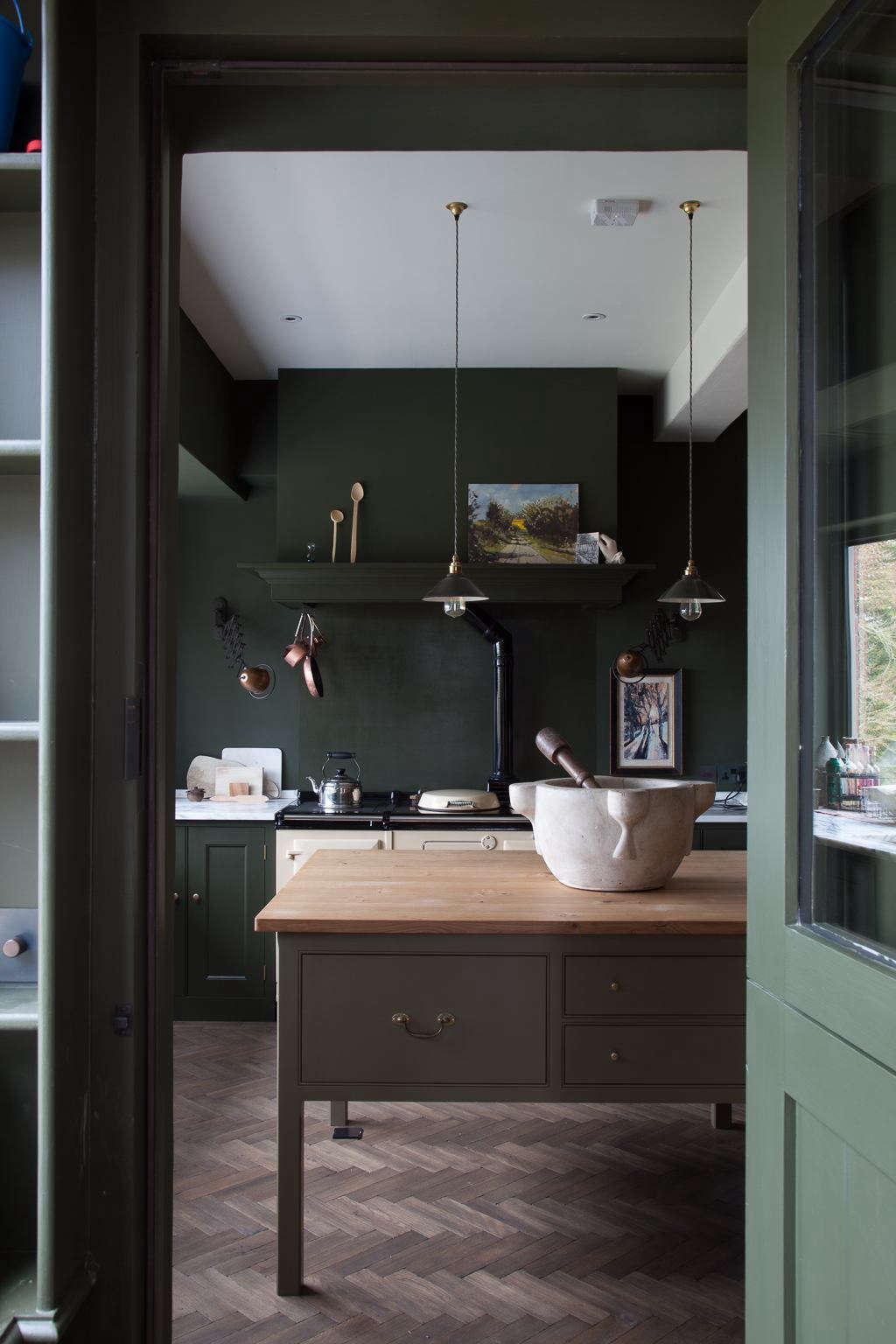 The canopy above the range conceals the vent hood and provides a subtle place for displaying art (the homeowner herself is an artist). The light shades are from Baileysin Ross-on-Wye. An oversize mortar and pestle makes a bold statement on the worktable.