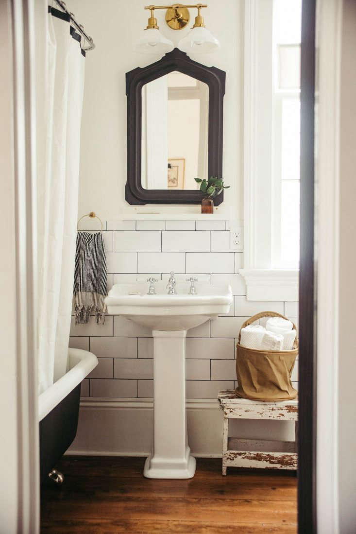 The first bathroom is tiled with the same subway tile as the kitchen. The pedestal sink is by Barclay, purchased from the local plumbing supply; the faucet is from Waterworks, and the double sconce is from Rejuvenation. The Turkish towel comes from Sunday Shopin New Orleans (Rosa is friendly with the designer-owners).