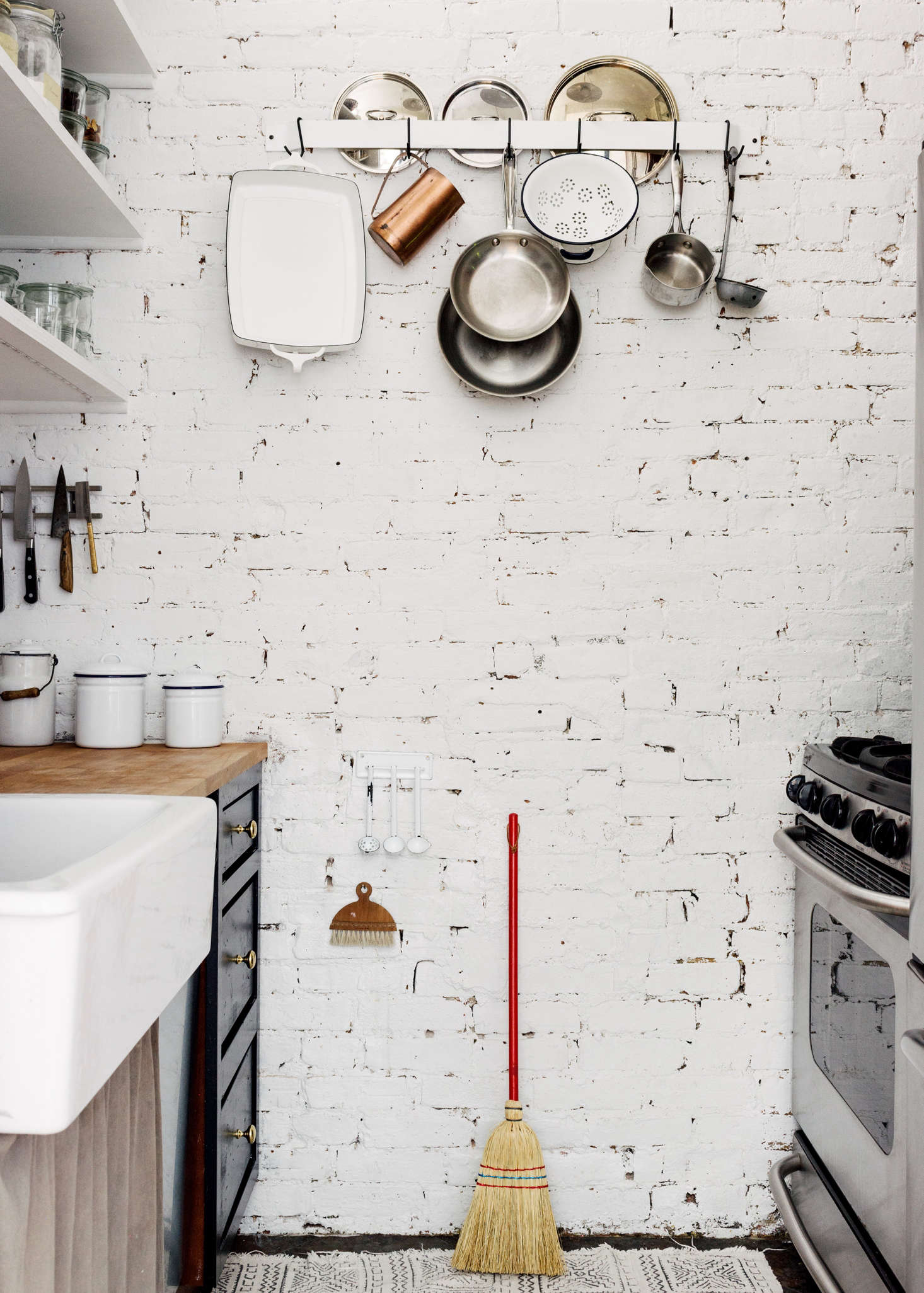 A red-handled broom provides a point of contrast to the white brick wall in Picture Room owner Sandeep Salter&#8