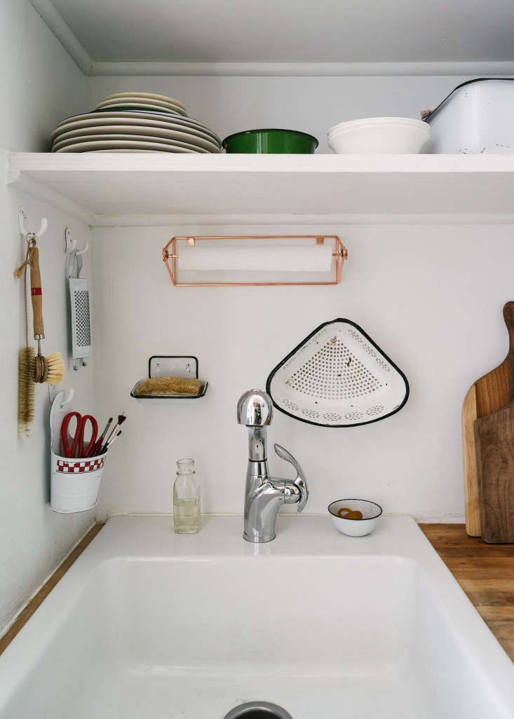 """A Modern FairyTale Told in 800 Square Feet Sandeep Salters Family Apartment """"I had no interest in enamelware until I met Carson,"""" says Sandeep. """"He grew up with so much of it in the South, and I realized it was a big part of my own visual vocabulary from England. So now we're both obsessed."""" Surrounding the sink is a collection of enamelware—a grater, a wall bucket, soap dish, and strainer—from various flea markets. Paper towels are kept in a Copper Wire Mountable Towel Holder from West Elm and the sink—""""a triumph; so affordable and the look and size is perfect""""—is the Domsjö from Ikea."""