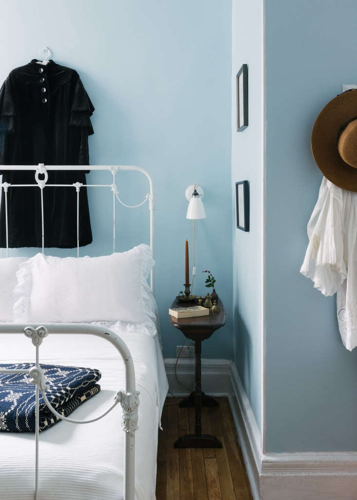"""A Modern FairyTale Told in 800 Square Feet Sandeep Salters Family Apartment """"I always wanted a Wedgwood Blue bedroom, but in reality, Wedgwood Blue proper was a little too dark for this room so we went with Farrow & Ball Parma Gray,"""" she says. """"It's a soothing color and reminds me of the last stanza of &#8\2\20;High Windows&#8\2\2\1;  and Marie Antoinette all at once!"""" The wrought iron bed frame is from a Goodwill in New Jersey with Stonewashed Belgian Linen bedding from Restoration Hardware. Behind the bed is a velvet overcoat from Sandeep's grandmother: """"very austere, as I believe she was."""""""