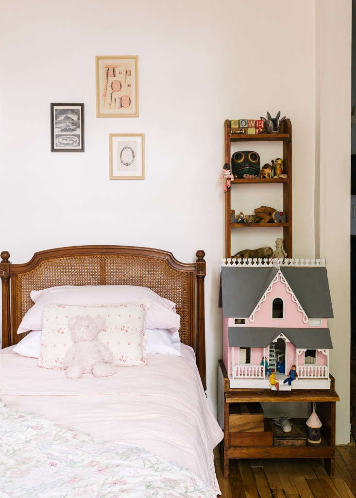 """A Modern FairyTale Told in 800 Square Feet Sandeep Salters Family Apartment The girls' bedroom has a rattan twin bed that was Carson's as a child. Above the bed are framed antique prints: """"Old Ideas of the World,"""" an \18th century German typographic form, and a wreath with the letter """"S."""" Sandeep built the dollhouse for their oldest daughter, Lowe Roma, while pregnant with their second, Eta, and furnished it with a Greenleaf Set found on eBay."""