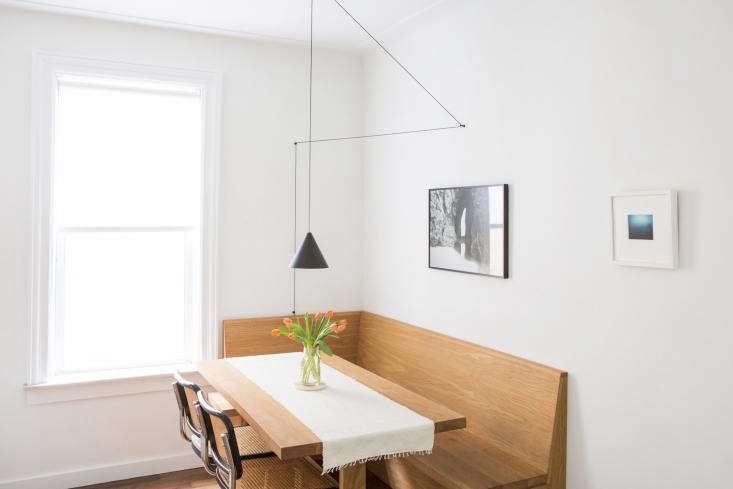 The homeowners wanted a built-in banquette, so Space Exploration designed a custom L-shaped bench of oil-finished white oak with matching trestle table, installed in a corner of the kitchen. The wall just beyond opens onto the living room.