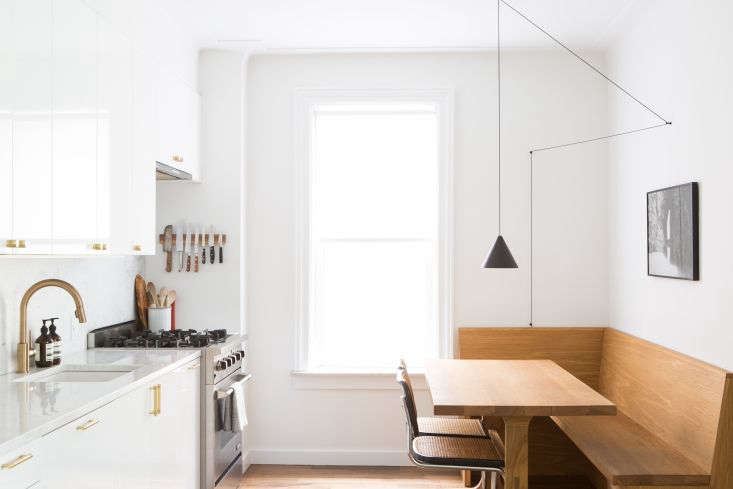 The countertop and backsplash are bianco gioia marble, and the apartment is painted throughout inWevet by Farrow & Ball.The kitchen window has its original casing.