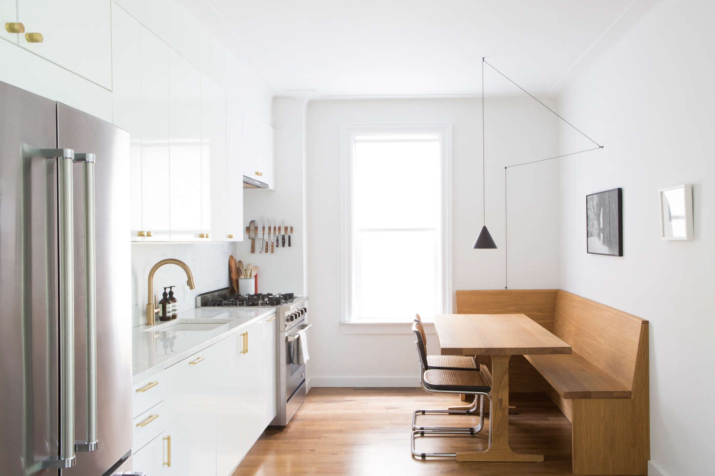 A Brooklyn kitchen by Space Exploration has basic Ikea cabinetry with glossy white cabinet fronts and marble countertops. For more, seeKitchen of the Week: An Ikea Kitchen with an Elegant Upper Cabinet Solution.
