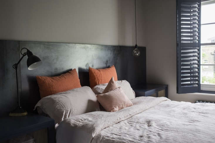 In the master bedroom, a steel headboard contrasts with the rumpled pastel linens; the bedside lamp is from Lampe Gras.