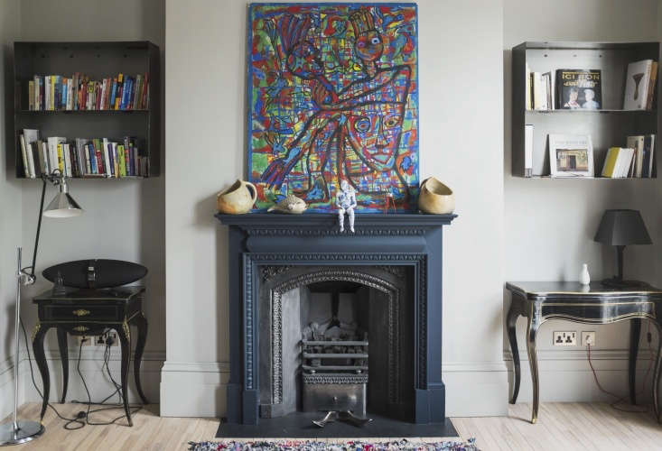 Estelle undertook the interior design and art direction; in the living area, a vintage Azilal Carpet anchors the room and a Lampe Gras Floor Lamp provides illumination. Two custom wall-mounted steel bookshelves flank the fireplace; the painting of a mother holding her children is from Kenya. &#8