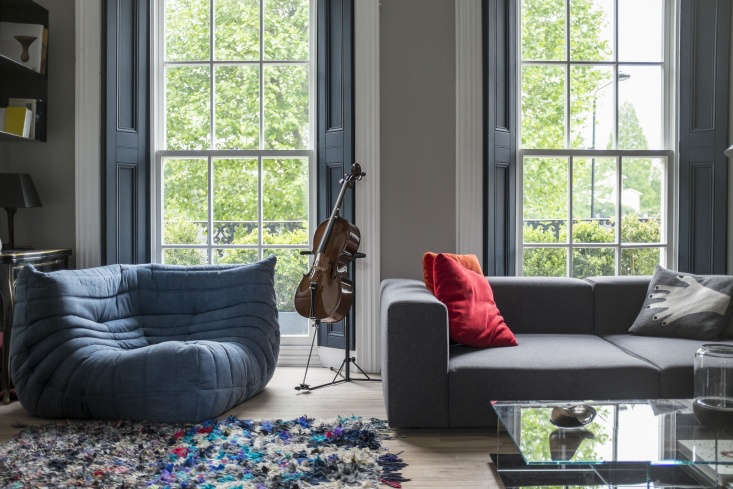 The L-shaped living space is flooded with natural light from three large sash windows. A Togo Fireside Chair, designed by Michel Ducaroy for Ligne Roset, anchors one corner of the room.