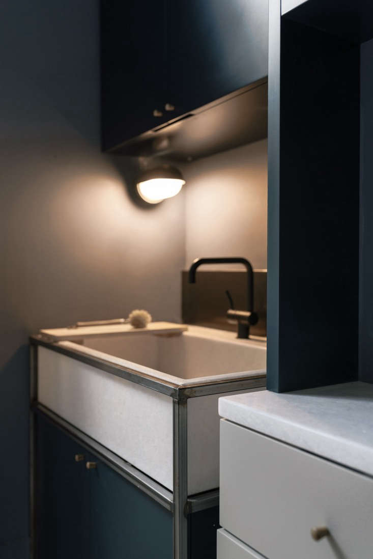 A closeup of the custom kitchen sink with welded steel stand; the sink is made from the same marble as the countertops.