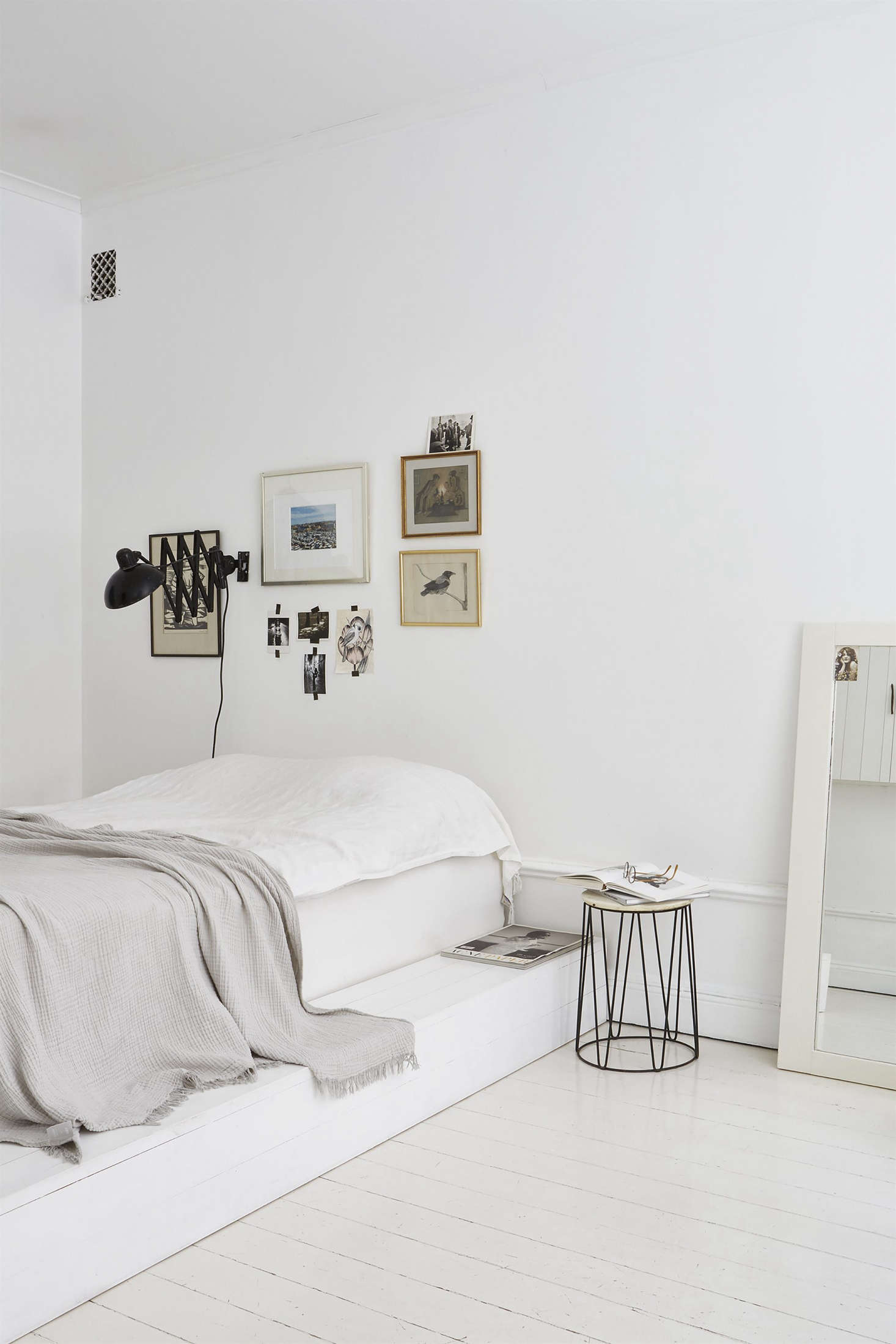 A white platform bed and inventive art arrangement at home in a Fantastic Frank apartment in Sweden styled by Josenfin Haag. Photograph by Emily Laye, courtesy of JH.