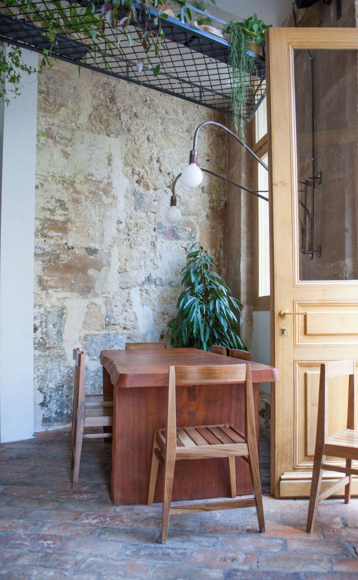 The restaurant is renovated with stone sourced from Italy and red brick found in an old house in Serbia. Sabrina and Stéphane thought about the interior design from a residential perspective, designing it like a home with houseplants, large wall mirrors, and versatile lighting.
