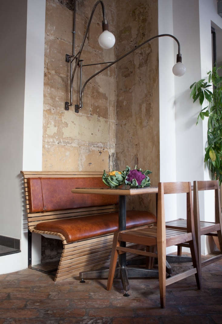 The furniture is all custom: slatted benches with leather cushions, oak chairs, and marble-top tables.