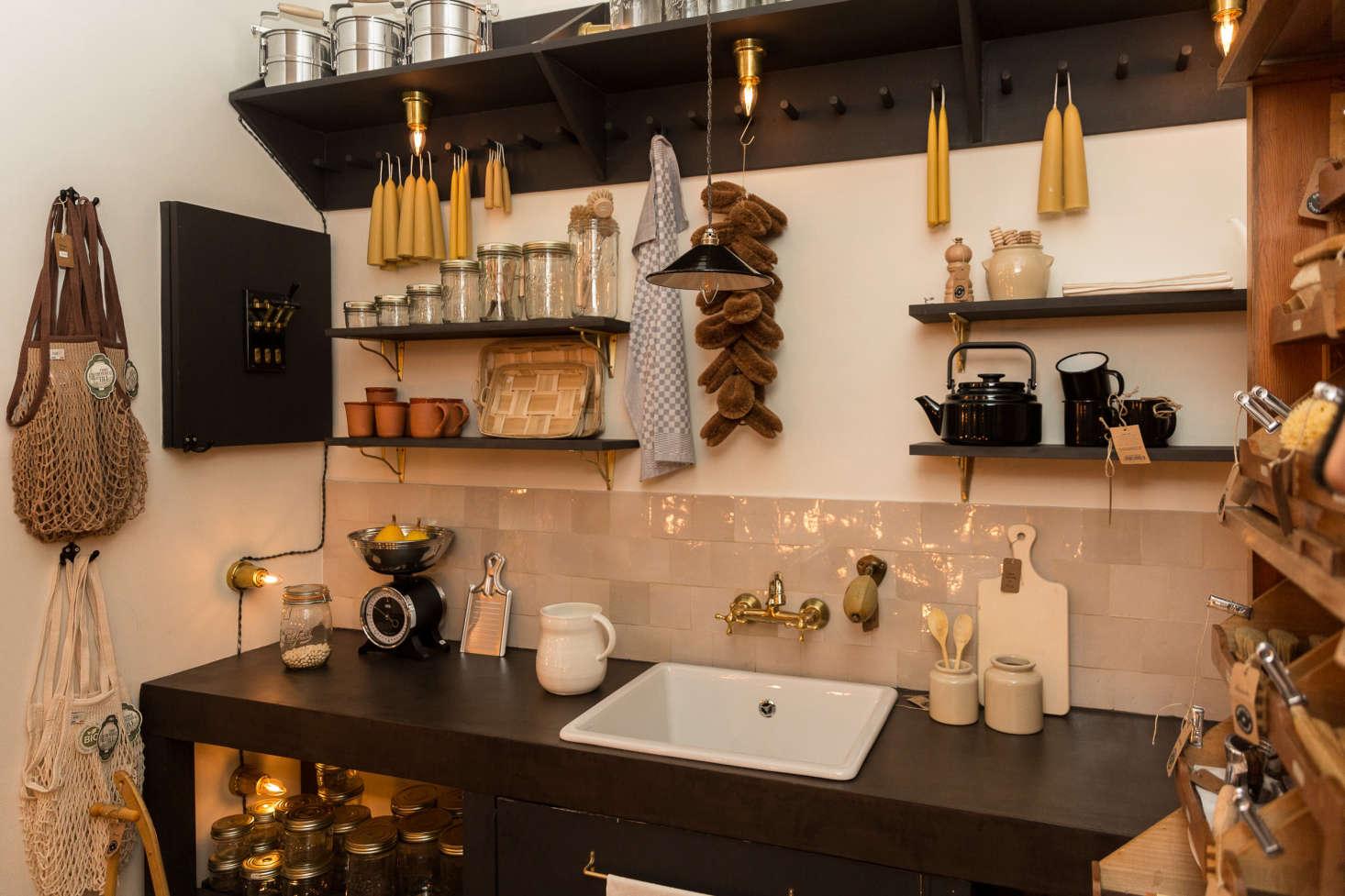 Kitchen accessories are arrayed around a concrete sink counter. The zellige backsplash tiles and brass bridge faucet are both Moroccan. The under-shelf brass sconces(€45) are a González &González design.