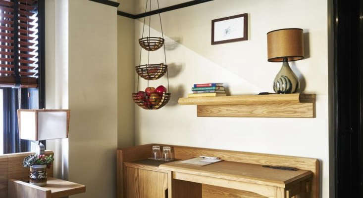 A quirky detail above a dorm-style desk: a hanging fruit basket.