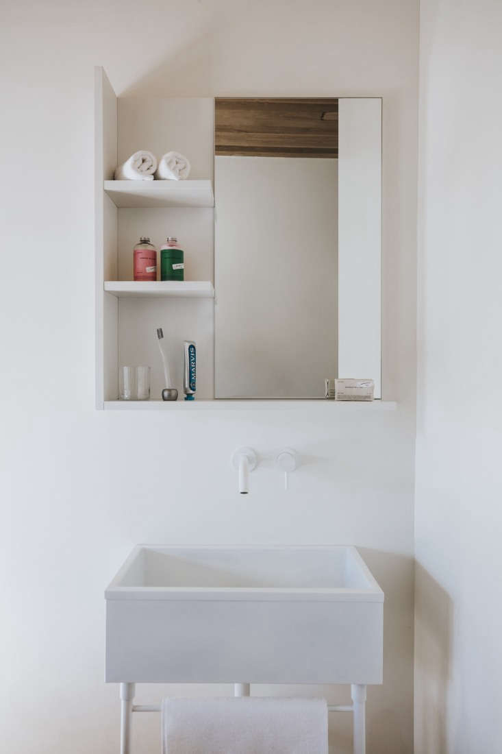Simple white sinks have Vola faucets.