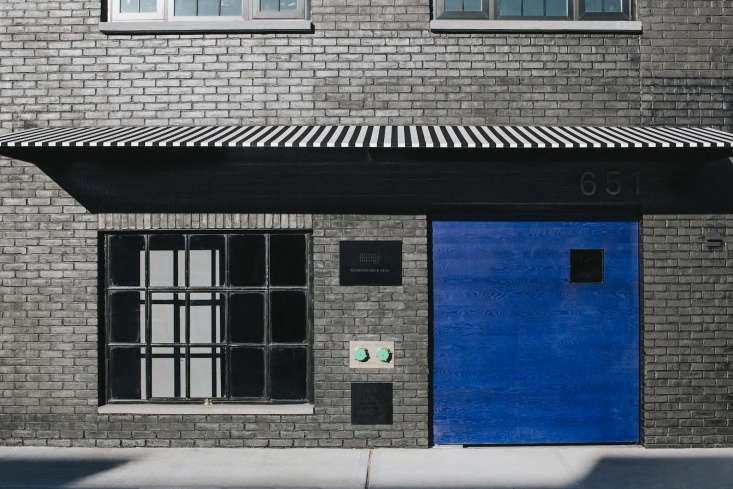 A black-and-white striped awning hangs over the the front entrance. The bright blue door is oak wood, stained in Yves Klein blue, in an iron frame.