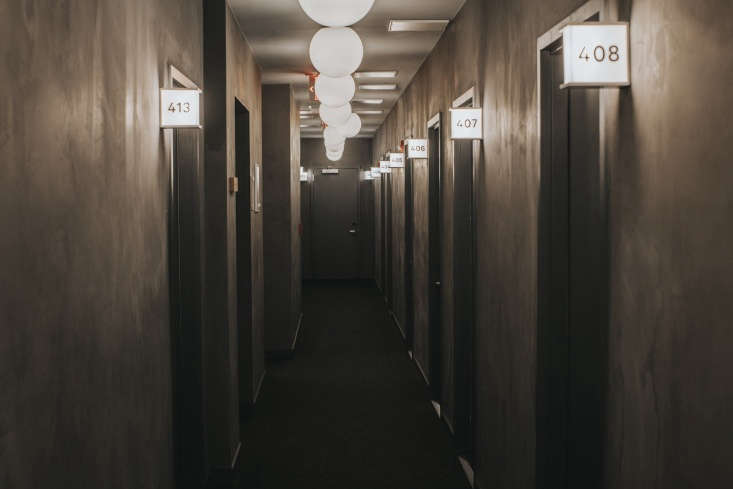 The hallways are finished in concrete. Vintage-style lighted squares serve as room signs.
